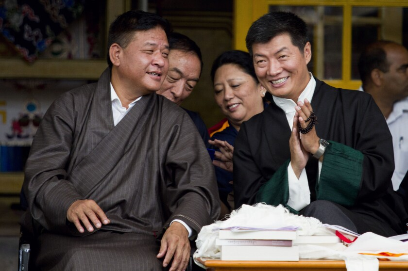FILE- In this Sept. 2, 2013 file photo, Prime Minister of the Tibetan government-in-exile Lobsang Sangay, right, listens to the Speaker of the Tibetan Parliament Penpa Tsering during the Tibetan Democracy Day celebrations at the Tsuglakhang temple in Dharmsala, India. Penpa Tsering has been elected the new president of the Tibetan government-in-exile, succeeding Lobsang Sangay who is completing two five-year terms each. (AP Photo/Ashwini Bhatia, File)