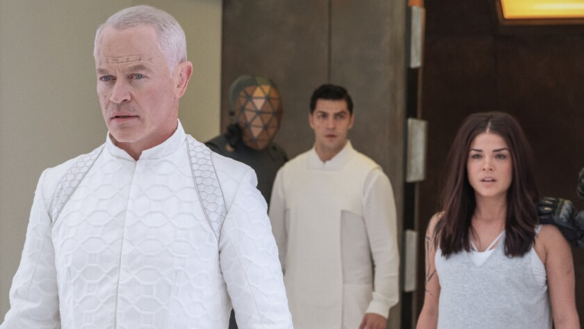 """Neal McDonough, left, Jason Diaz and Marie Avgeropoulos in a scene from """"The 100"""" on the CW"""