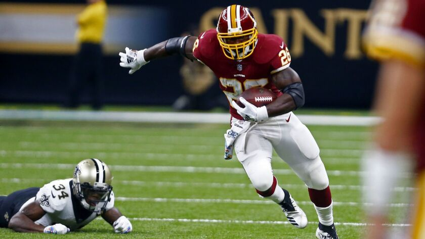 Redskins running back Adrian Peterson carries the ball past New Orleans Saints defensive back Justin Hardee.