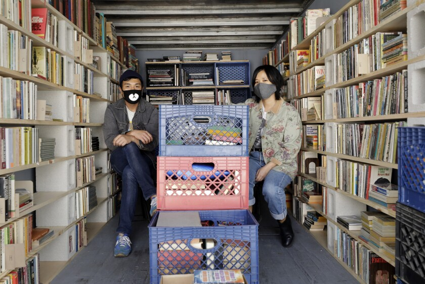 Chris Capizzi and Jenny Yang in one of the two Atwater Village storage lockers that hold inventory for their pop-up bookselling business, A Good Used Book.