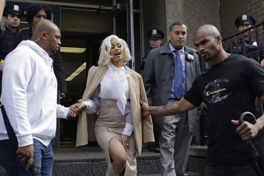 Cardi B is assisted by security guards as she leaves a police precinct Monday, Oct. 1, 2018, in the Queens borough of New York. The rapper met with police as part of an investigation of her possible involvement in a fight at a strip club.