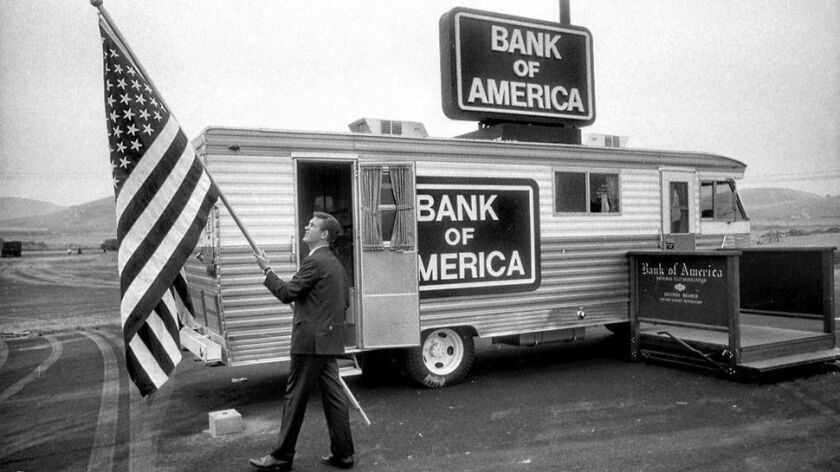 Richard D. Ayers raising flag out front of Bank of America's traveling bank RV in West Covina, Calif