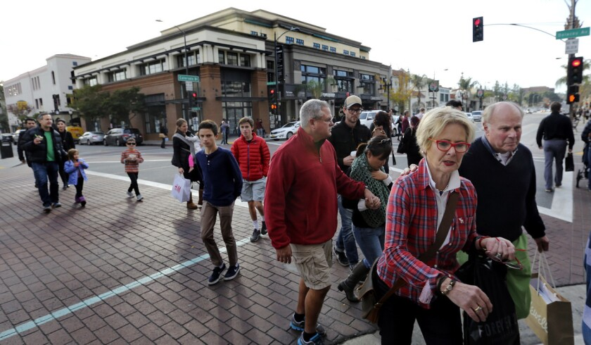 Pedestrians make their way across the street on Colorado Blvd. in Pasadena on Dec. 24.