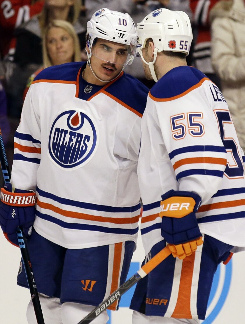 Edmonton Oilers right wing Nail Yakupov, left, talks with center Mark Letestu during the second period of an NHL hockey game against the Chicago Blackhawks, Sunday, Nov. 8, 2015,  in Chicago. (AP Photo/Nam Y. Huh)