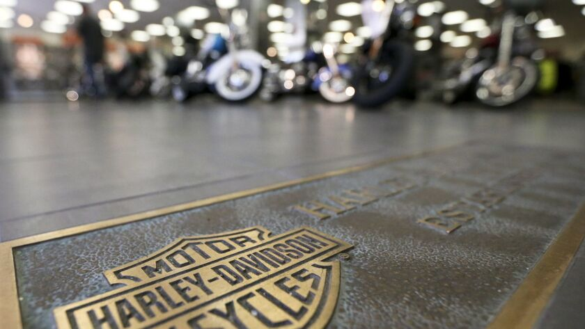 FILE - In this April 26, 2017, file photo, rows of motorcycles are behind a bronze plate with corpor