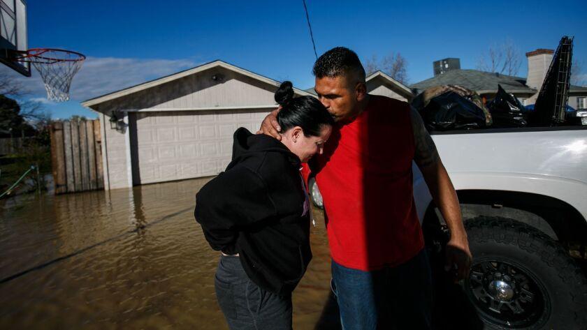 Juan Álvarez reconforta a su novia, Sarah Hendrix, luego de ayudarla a mudarse de su casa inundada en Maxwell, California (Marcus Yam / Los Angeles Times).