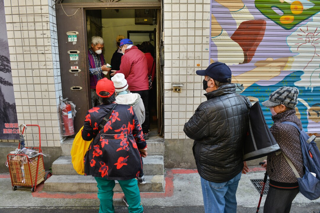 Low-income people queue up to receive one of the twice-daily meals in Taipei's Wanhua District.