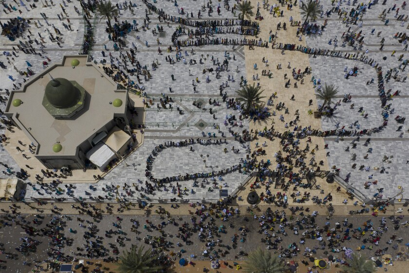 In this aerial photo taken with a drone, pilgrims from the Mouride Brotherhood arrive at the Grand Mosque of Touba during the celebrations of the Grand Magal of Touba, in Senegal, Tuesday, Oct. 6, 2020. Despite the coronavirus pandemic, thousands of people from the Mouride Brotherhood, an order of Sufi Islam, gather for the annual religious pilgrimage to celebrate the life and teachings of Cheikh Amadou Bamba, the founder of the brotherhood. (AP Photo/Leo Correa)