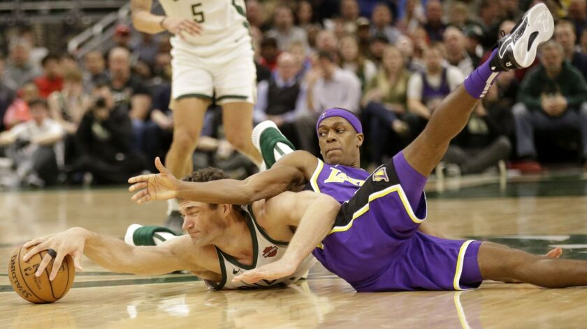 Milwaukee Bucks' Brook Lopez, left, and Los Angeles Lakers' Rajon Rondo reach for a loose ball durin