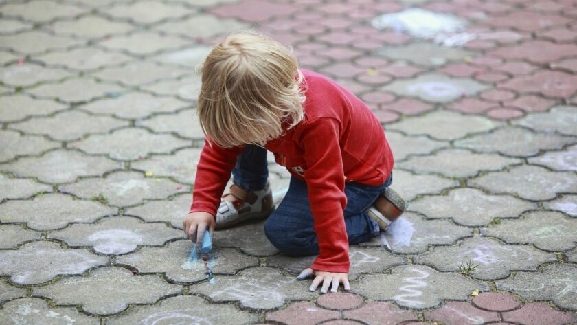 Preschooler child drawing with chalk on sidewalk daycare nursery generic web stock