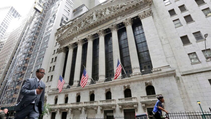 FILE- In this Oct. 24, 2017, file photo, people pass the New York Stock Exchange. The U.S. stock mar