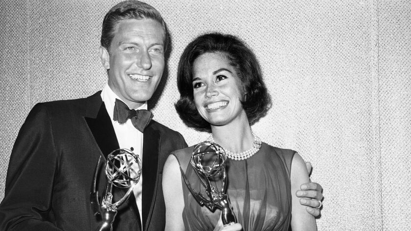 This May 25, 1964 file photo shows Dick Van Dyke and Mary Tyler Moore backstage at the Palladium with their Emmys for best actor and actress in a series at the Television Academy's 16th annual awards show, in Los Angeles.
