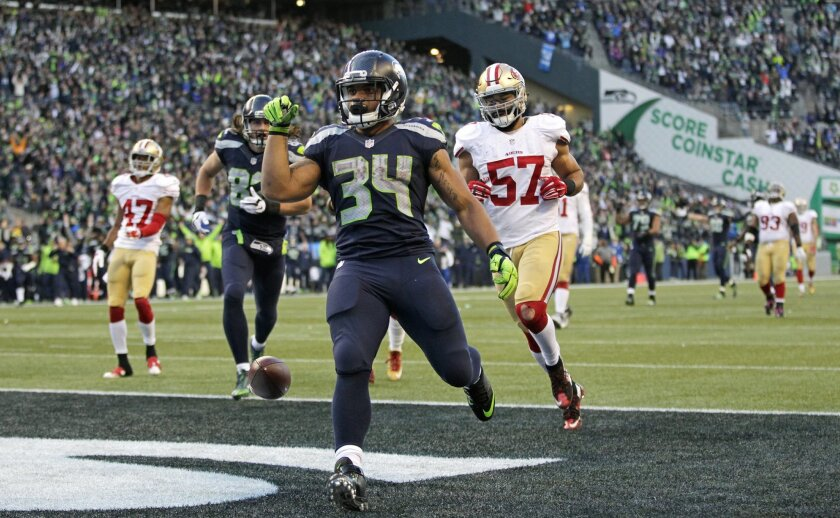 Seattle Seahawks running back Thomas Rawls (34) drops the ball after scoring a touchdown ahead of San Francisco 49ers inside linebacker Michael Wilhoite (57) during the second half of an NFL football game Sunday, Nov. 22, 2015, in Seattle. (AP Photo/John Froschauer)