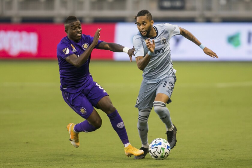 FILE - Sporting Kansas City defender Amadou Dia (13) attempts to maneuver past the defense of Orlando City midfielder Sebas Mendez (8) during an MLS soccer game in Kansas City, in this Wednesday, Sept. 23, 2020, file photo. Major League Soccer has extended its deadline for negotiating adjustments to the existing collective bargaining agreement until Feb. 4 and warned it is prepared to lock out players if a deal isn't reached by then. (Nick Tre. Smith/The Kansas City Star via AP, File)