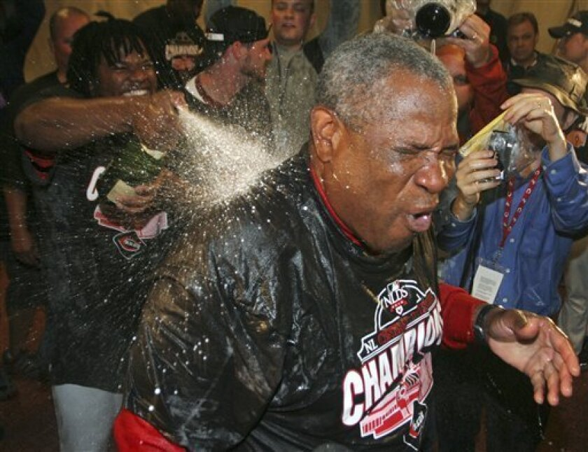 Cincinnati Reds manager Dusty Baker is sprayed with champagne by pitcher Johnny Cueto, left, after the Reds defeated the Houston Astros 3-2 in a baseball game to clinch the NL Central, Tuesday, Sept. 28, 2010, in Cincinnati. (AP Photo/Tom Uhlman)