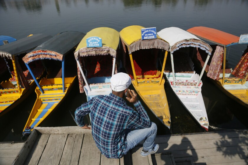 A Kashmiri boatman talks on his cellphone as he sits on the banks of the Dal Lake in Srinagar, once home to several Pandits.