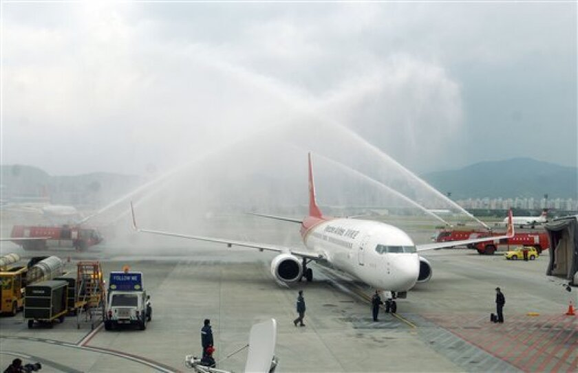 The day's first direct flight from Shenzhen, mainland China arrives at Taipei's Sungshan Airport, Monday, Dec. 15, 2008. China and Taiwan have started a new era of direct air and shipping services Monday with planes and ships travel directly across the Taiwan Strait, formally ending a nearly six-decade ban on regular links. (AP Photo/Chiang Ying-ying)