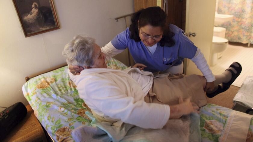 A home health aide helps a woman get out of bed. Long-term care can cost tens of thousands of dollars a year.