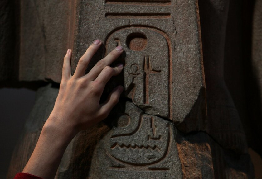 Angel Ayala touches a quartzite likeness of Ramesses II at the Penn Museum in Philadelphia, Monday Nov. 25, 2013. Ayala, 16 and blind since birth, touched ancient Egyptian artifacts at the University of Pennsylvania archaeology museum as part of a special tour for the blind and visually impaired. (AP Photo/Jacqueline Larma)