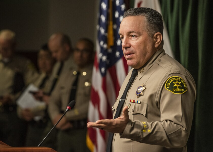 Sheriff Alex Villanueva, in front of a microphone, speaks to the media in March.