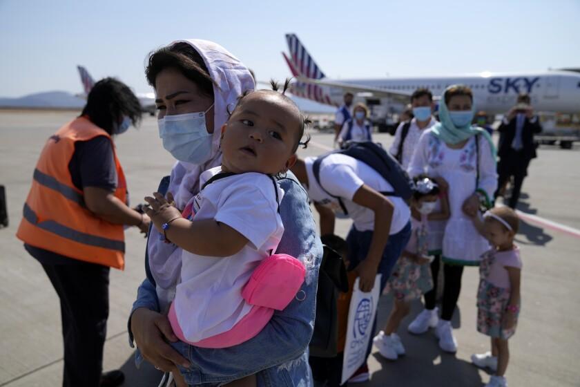 Refugiados afganos abordan un avión a Portugal en el Aeropuerto Internacional Eleftherios Venizelos de Atenas, martes 28 de setiembre de 2021. (AP Foto/Thanassis Stavrakis)