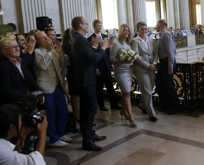 Sandy Stier, center left, and Kris Perry are greeted with applause as they prepare to be wed by California Attorney General Kamala Harris at City Hall in San Francisco, Friday, June 28, 2013. Stier and Perry, the lead plaintiffs in the U.S. Supreme Court case that overturned California's same-sex m