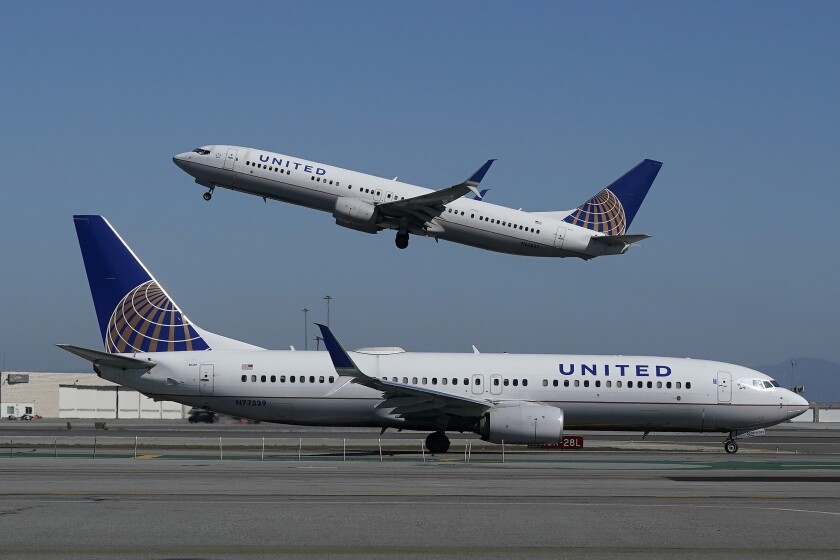 An airplane takes off in San Francisco while another plane is parked in the forefront.