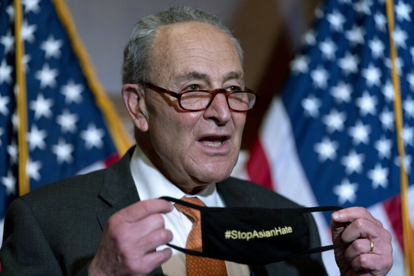 Senate Majority Leader Chuck Schumer of N.Y., holds up his mask that reads #StopAsianHate as he speaks at a news conference after the Senate passes a COVID-19 Hate Crimes Act on Capitol Hill, Thursday, April 22, 2021, in Washington. (AP Photo/Andrew Harnik)