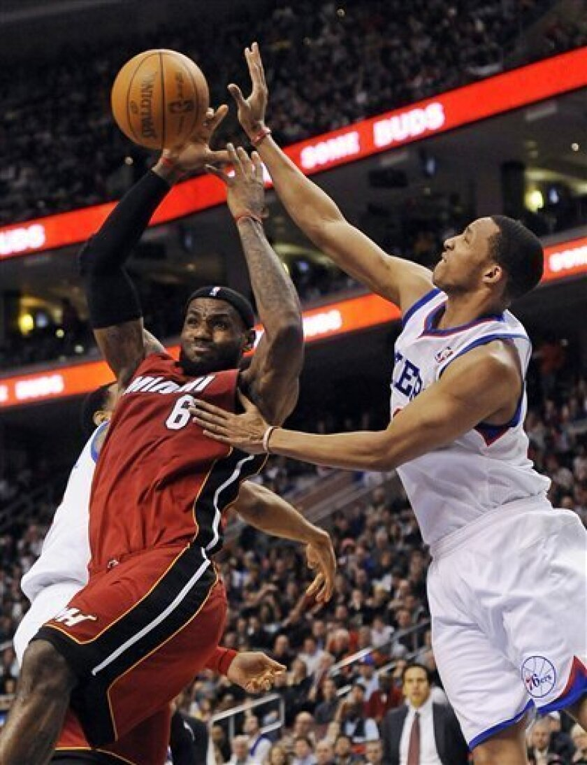 Miami Heats' LeBron James (6) is fouled by Philadelphia 76ers' Evan Turner (12) in the first half of an NBA basketball game on Friday, Feb. 3, 2012, in Philadelphia. (AP Photo/Michael Perez)