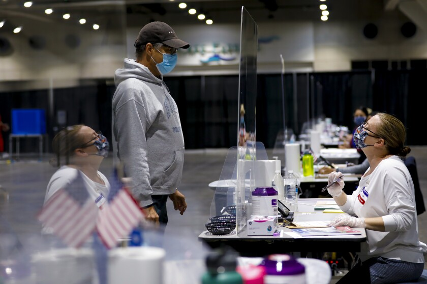 At the San Diego Convention poll location, Mika Bursch checks in to vote