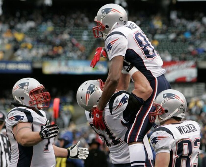 New England Patriots wide receiver Randy Moss, top, is hoisted by teammates after making a 20-yard touchdown reception against the Oakland Raiders during the first half on an NFL football game in Oakland, Calif., Sunday, Dec. 14, 2008. (AP Photo)