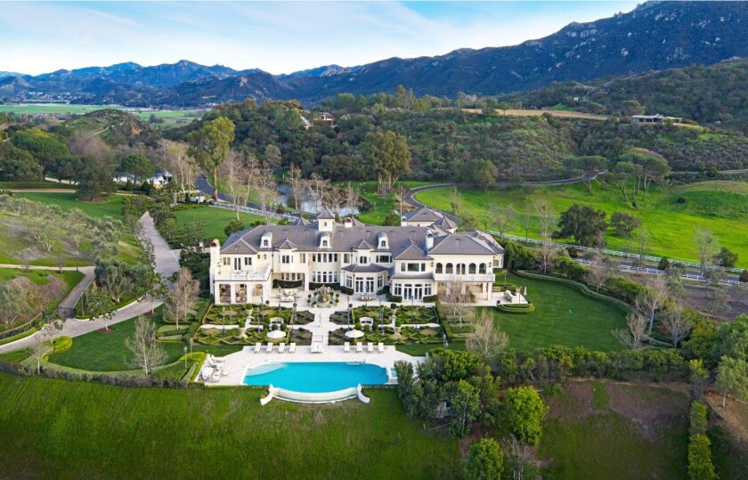 An aerial view shows a mansion and pool amid green lawns and tree-covered hills with mountains as a backdrop.