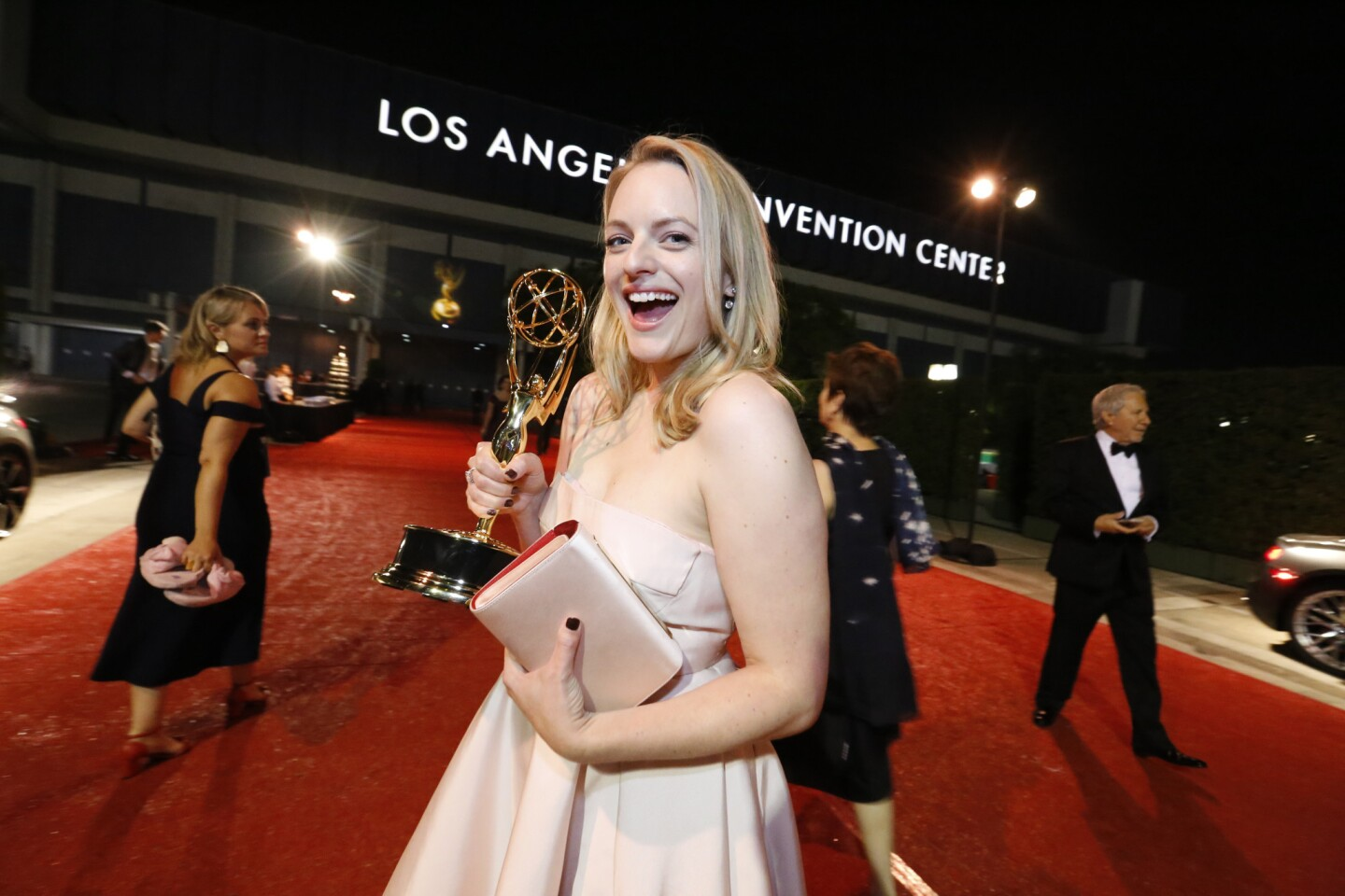 """Elisabeth Moss, who won the lead actress in a drama series Emmy for her work on """"The Handmaid's Tale,"""" poses with her statue in front of the convention center."""