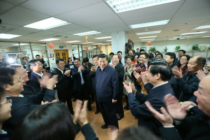 In this photo released by China's Xinhua News Agency, people applaud as Chinese President Xi Jinping, center, talks with editors in the general newsroom of the People's Daily in Beijing, Friday, Feb. 19, 2016. Chinese President Xi Jinping made a rare, high-profile tour of the country's top three st