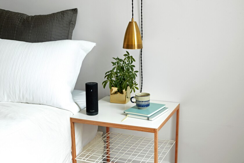 An Amazon Tap sits on a bedside table.