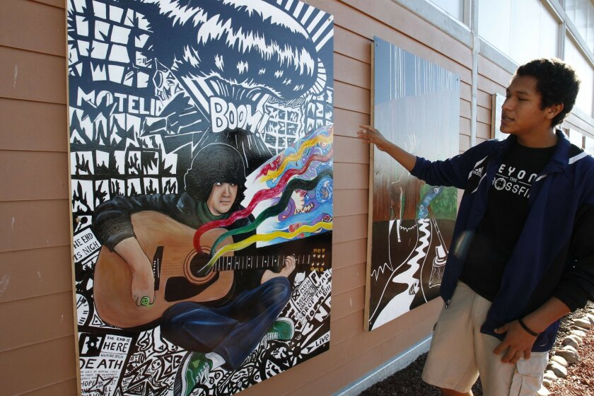 Alec Martinez, a Junior at High Tech High in Chula Vista, explained some of the symbolism in a campus mural that portrays Sean Fuchs, a High Tech student who was killed along with his brother Kyle in 2011, at the front of the school.