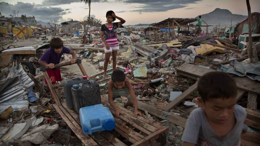 Children in Tacloban, Philippines, push a cart on Nov. 18, 2013, as they collect water in an area destroyed by Typhoon Haiyan.