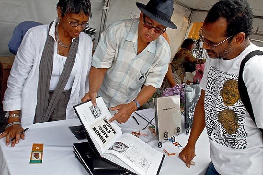 A woman and two men look at a book at the Leimert Park Book Fair, returning Saturday.