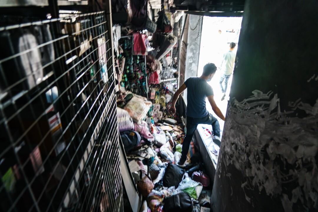 یک مغازه دار یک مغازه آسیب دیده در اثر حملات را در شهر غزه ترک می کند.