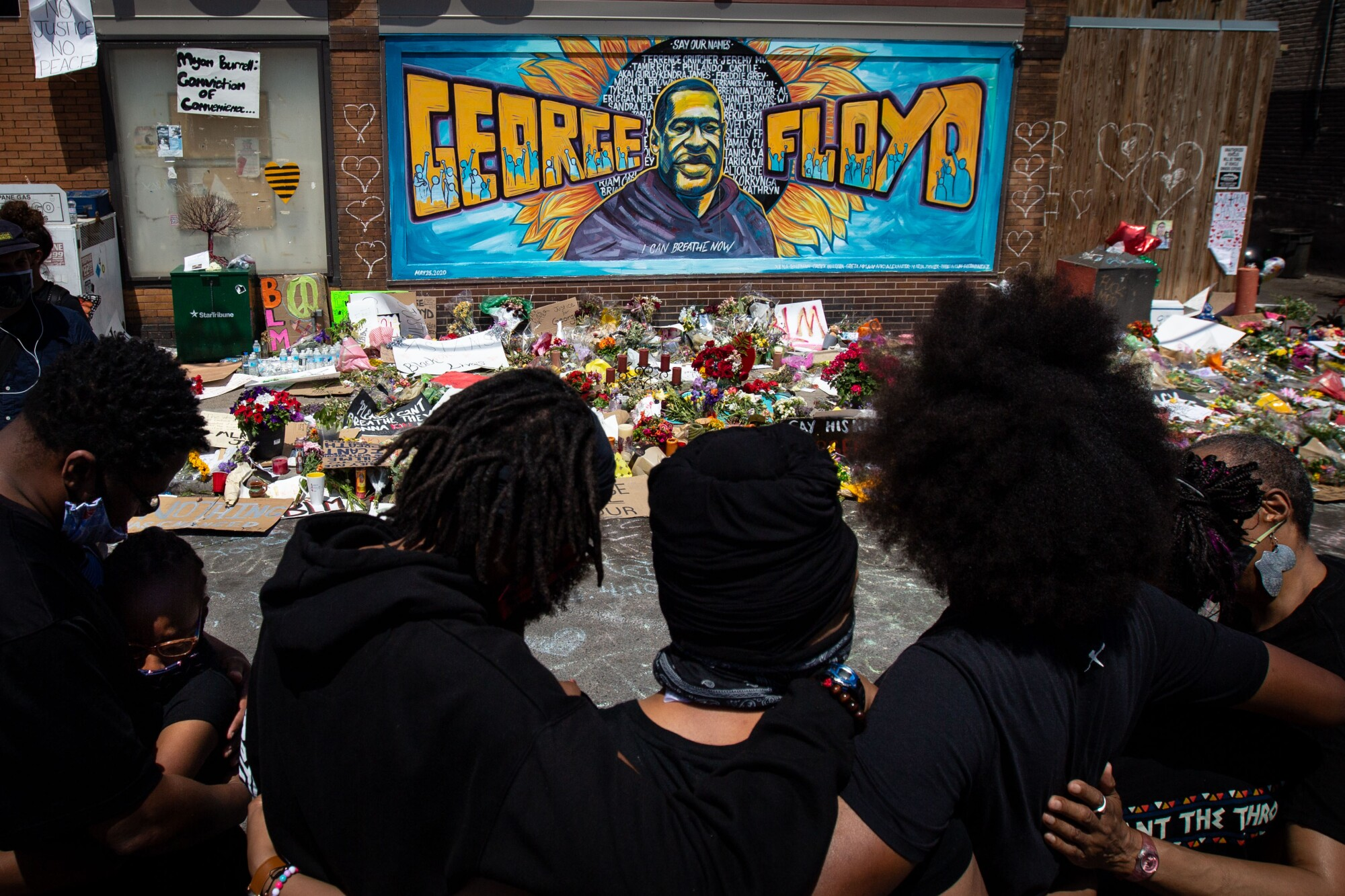 The Holloway family of Minneapolis pays respects in front of Cup Foods where George Floyd was killed.