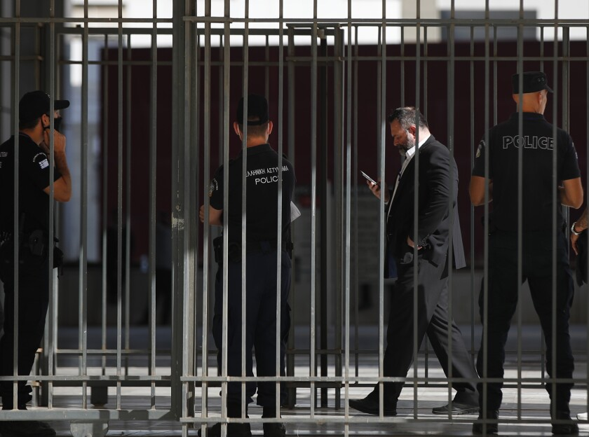European Parliament member Ioannis Lagos, who had been found guilty along with others of leading a criminal organization and face five to 15 years in prison, uses his mobile phone outside a court, waiting for his sentencing in Athens, Monday, Oct. 12, 2020. An Athens court has extended to Monday a sentencing hearing for leading members and associates of Greece's far-right Golden Dawn convicted earlier this week of multiple crimes. (AP Photo/Thanassis Stavrakis)