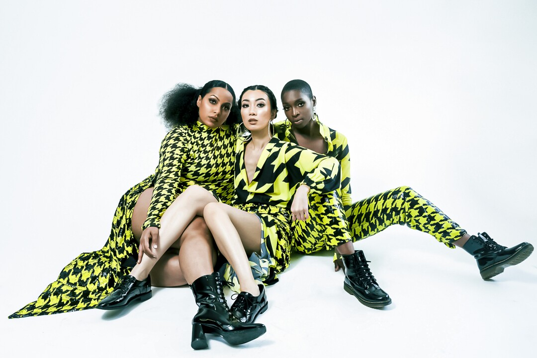 Three women wearing clothes covered in houndstooth checks.