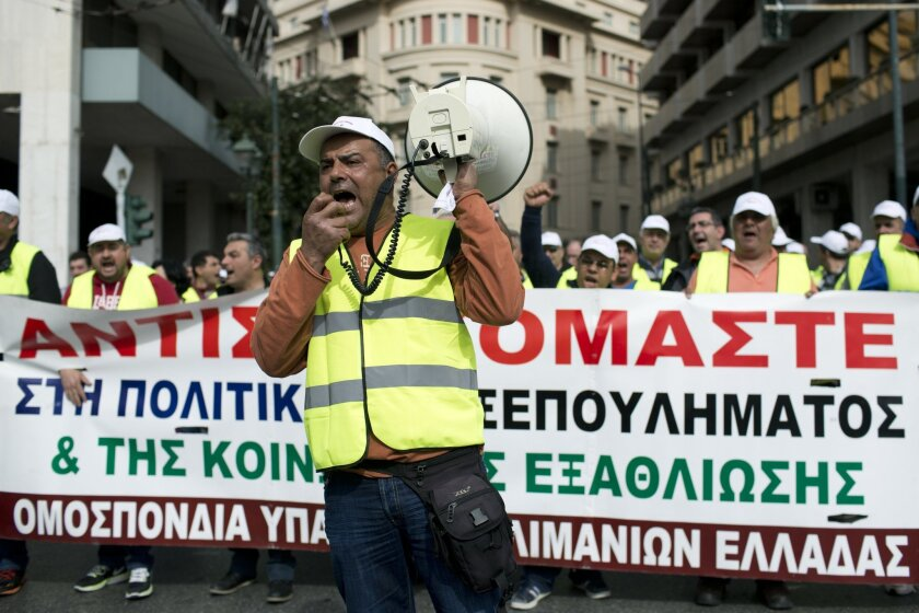 Dock workers chant anti austerity slogans as they carry a banner which reads ''we resist'' during a protest in central Athens, on Wednesday, Feb. 17, 2016. Greek dock workers have started a two-day strike protesting against the privatization of country's biggest ports. (AP Photo/Petros Giannakouris