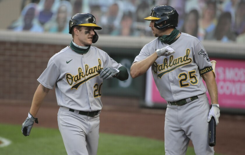 Oakland Athletics' Mark Canha, left, greets Stephen Piscotty (25) after Canha scored during the fifth inning of a baseball game against the Seattle Mariners, Monday, Aug. 3, 2020, in Seattle. (AP Photo/Ted S. Warren)