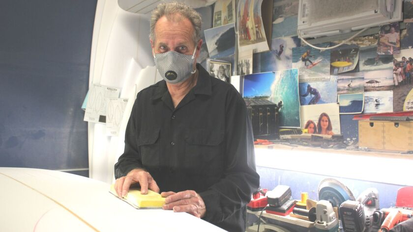 La Jolla craftsman and designer Tim Bessel shapes a surfboard blank at his Westbourne Street workshop, March 1.