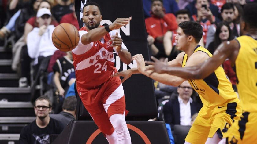 Raptors guard Norman Powell passes the ball after driving against Pacers forward Doug McDermott during the second half Sunday.