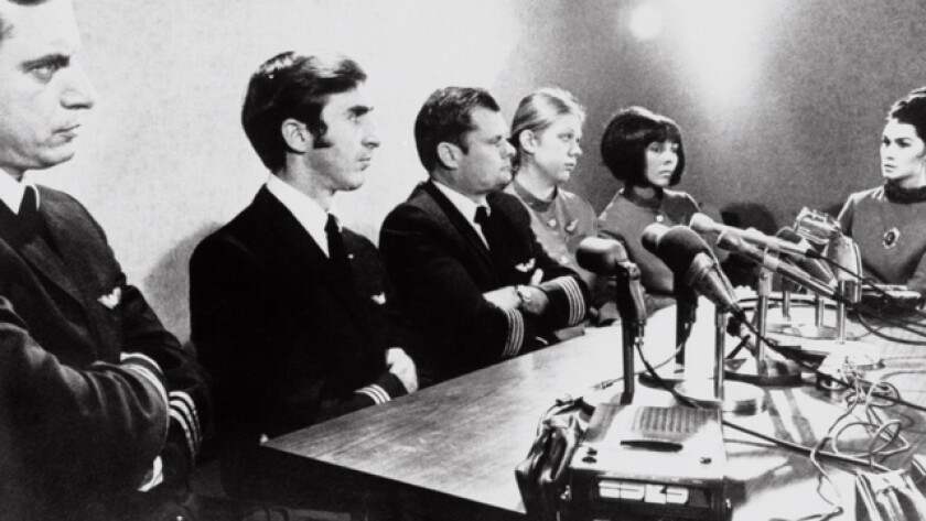 The crew of the plane hijacked by D.B. Cooper sits at a table behind a bank of microphones and a tape recorder.