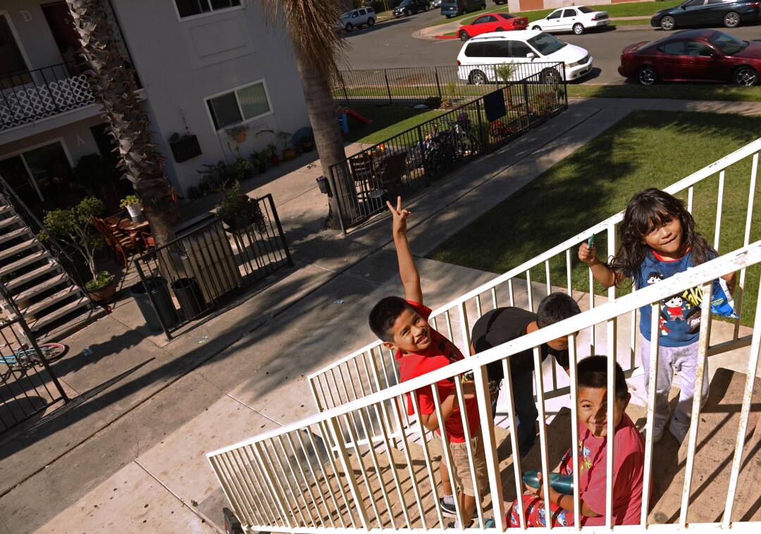 Children play on the staircase in front of their apartment in Oak View.