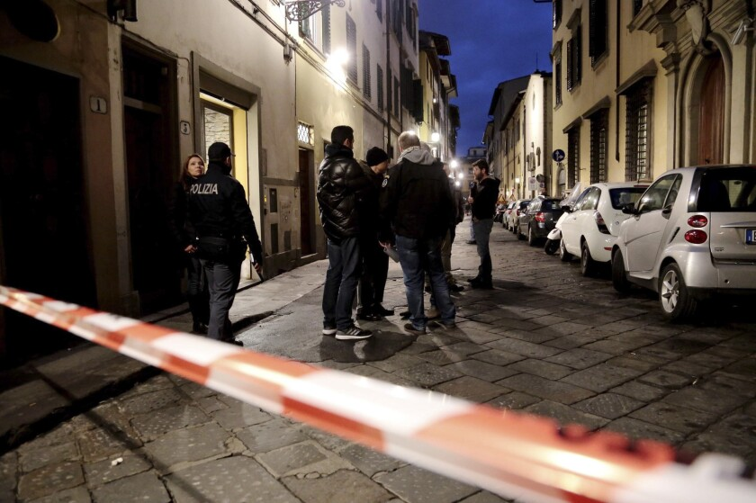 Italian police officers stand outside an apartment where Ashley Oslen, an American woman, was found dead in Florence on Saturday.