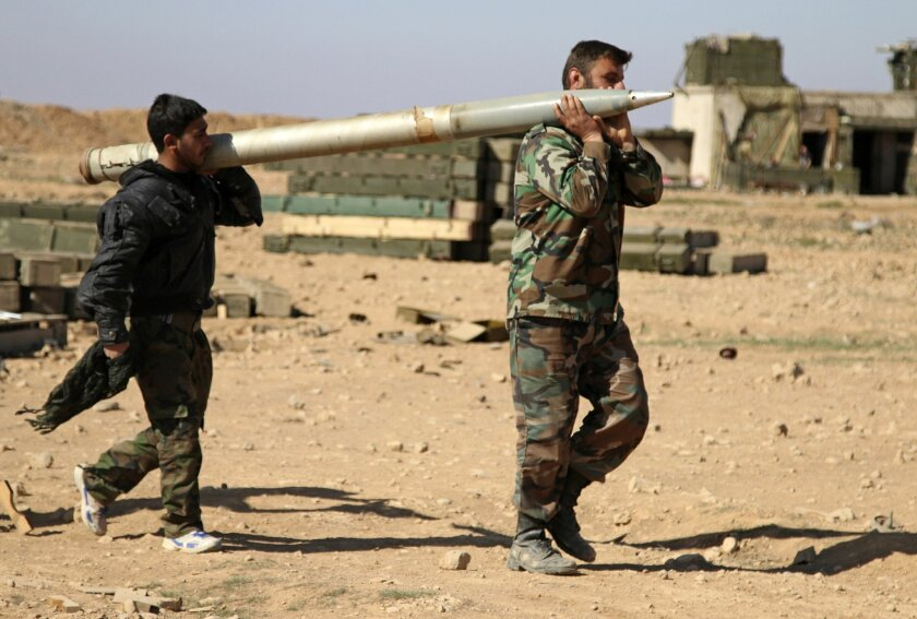 In this photo taken on Wednesday, Feb. 17, 2016, soldiers from the Syrian army carry a rocket to fire at Islamic State group positions in the province of Raqqa, Syria. In recent weeks, Syrian government forces captured dozens of villages and towns across the country. (Alexander Kots/Komsomolskaya Pravda via AP)